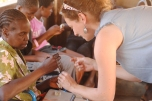 Rebecca training an orphan caregiver in a sewing project